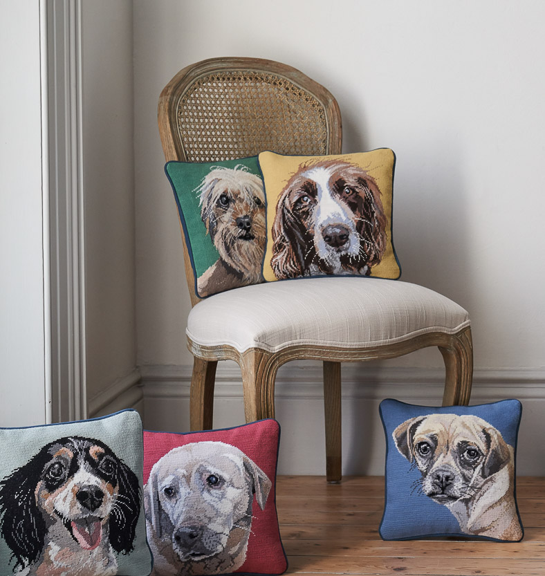 A chair with completed needlepoint tapestry cushions with various portraits of dogs.