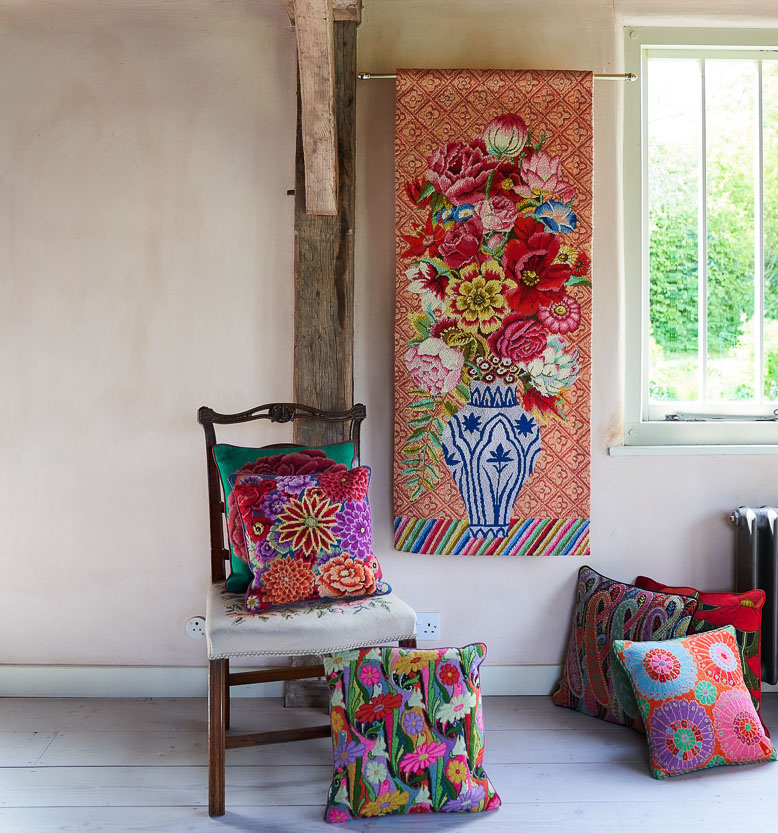 An arrangement of completed needlepoints including a large hanging tapestry with a floral motif