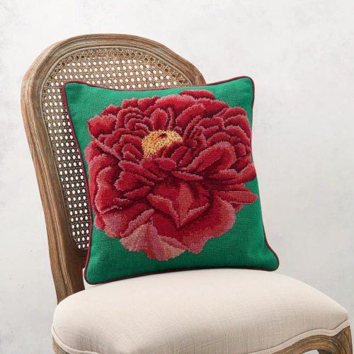 A needlepoint cushion of a bright red peony set on a green background photographed on a chair